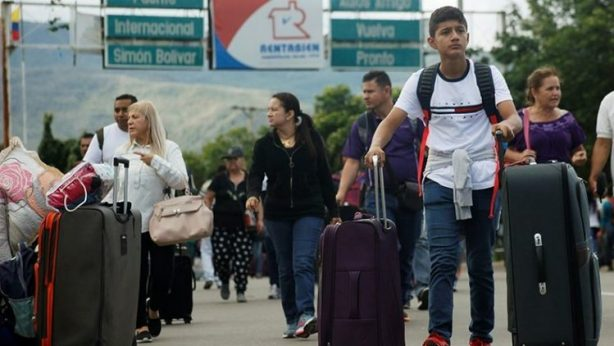 Venezuelans with suitcases walking to cross border