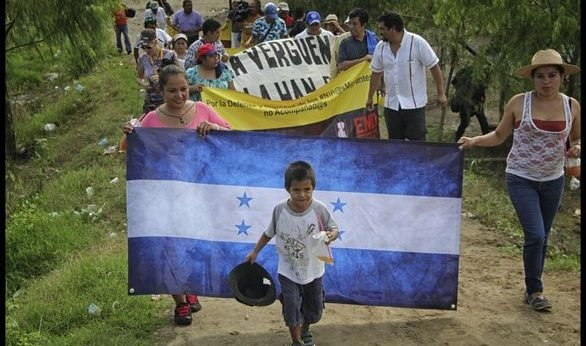 Hondurans walking in caravan carrying Honduras flag