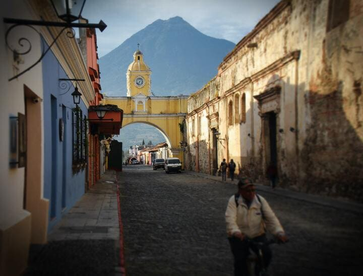 man biking in front of Antigua Guatemala's Santa Catalina arch