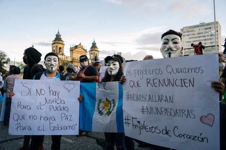 Guatemalan protestors holding signs  renouncing government corruption