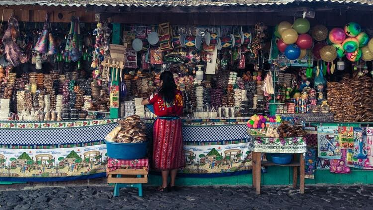Guatemalan woman working at market dulces tipicos (traditional sweets) stand